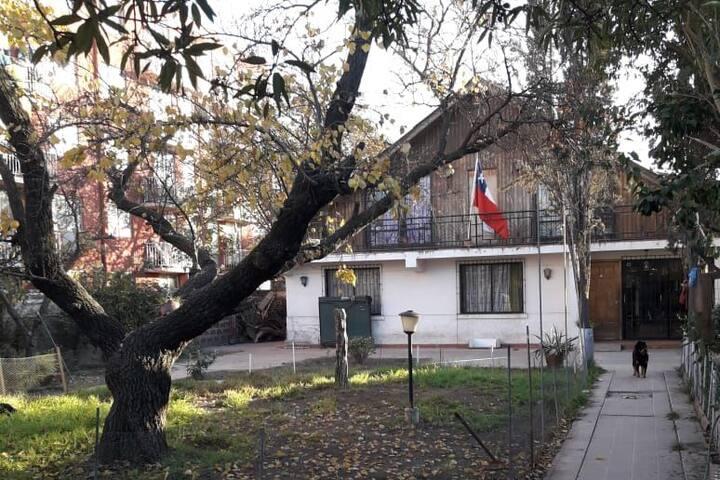 El patio delantero y entrada  de la casa. la habitación es la que está abajo de la bandera.