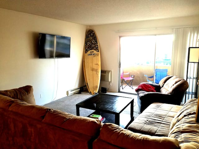 Huge living with comfy sectional couch and smart TV.  Entrance to large balcony area with furniture for outdoor relaxation.