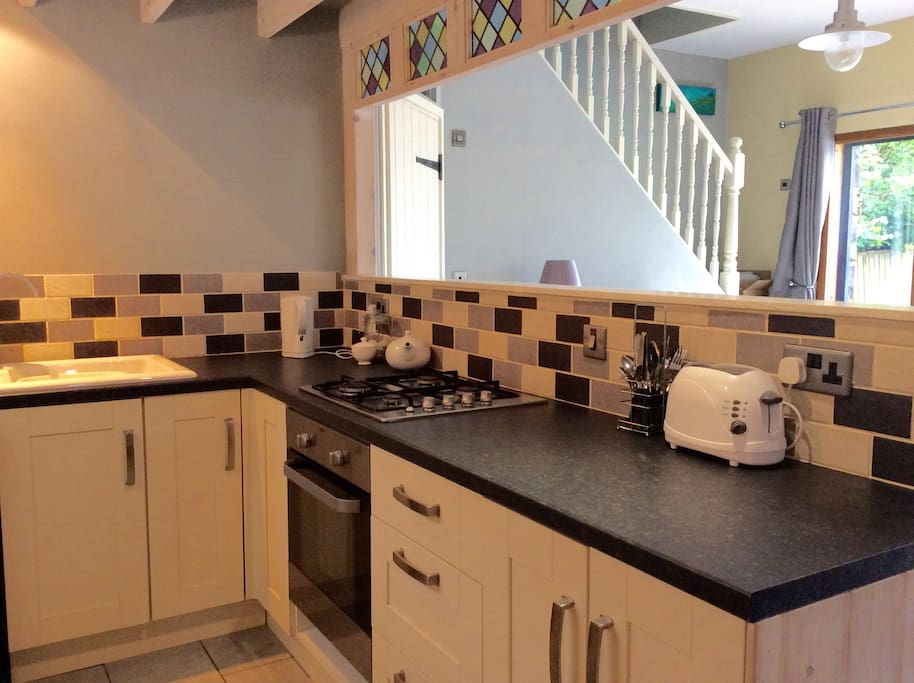 Modern fitted kitchen with cooker, washing machine, microwave and fridge freezer