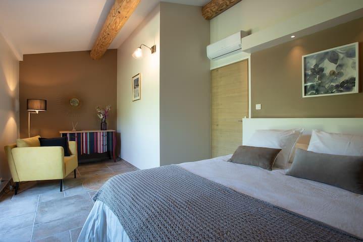 Large bedroom including a lounging area, grande chambre avec petit coin salon