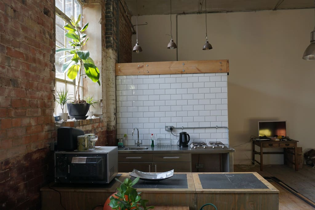 Kitchen area with metro tiles and vintage industrial lighting add to the look.