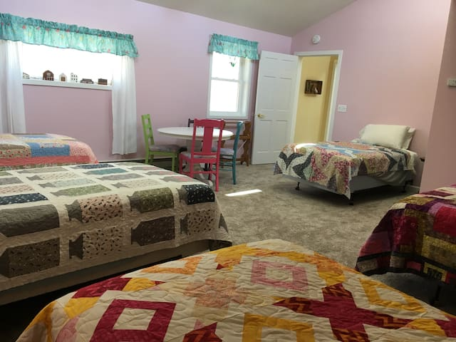 The upstairs bedroom has 1 queen bed and 4 twins.  They all have homemade quilts on the beds.