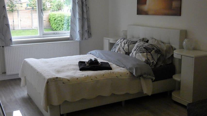 Zeer stille en ruime slaapkamer met luxe 2 persoons hoge boxspring en brede 2 persoonslaapbank, aparte wasbak en veel kastruimte. Room divider aanwezig. De slaapkamer heeft tuinzicht
