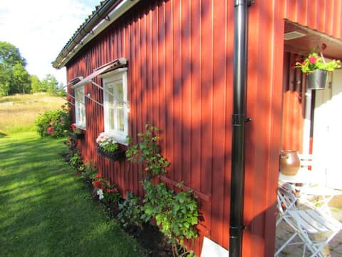 Red cottage on a farm nearby a litte lake