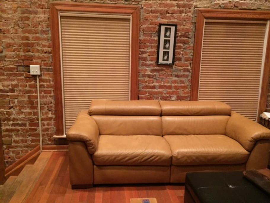Modern living room with exposed brick walls and double automated reclining leather couch