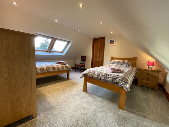 Roomy twin bedroom upstairs with view to hills.