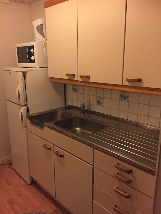 Kjøkkenkrok med diverse utstyr (vannkoker, service, bestikk, kjøle/fryseskap, komfyr og et lite kjøkkenbord med 2 stoler).