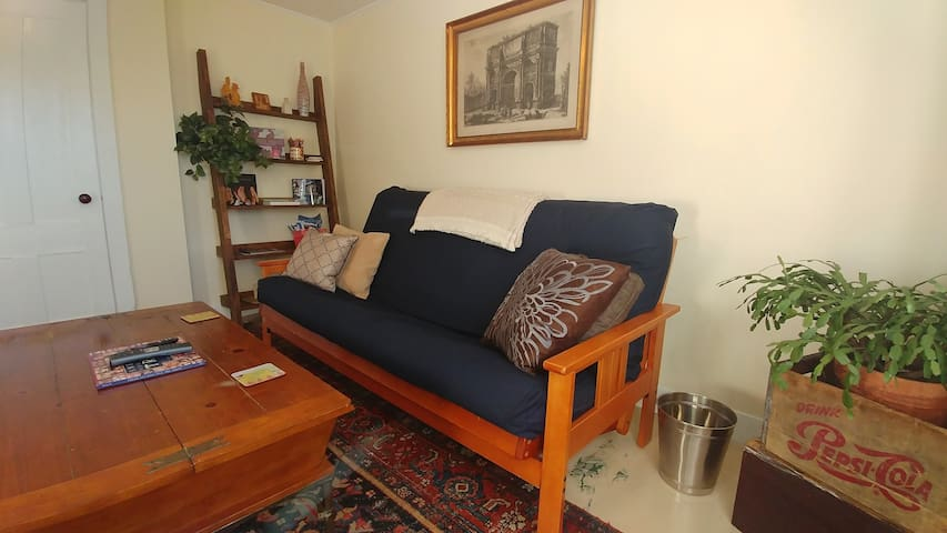 The living room is casually furnished with traditional art and a lovely old oriental rug. A surprisingly comfortable futon to relax or sleep on. There's info on the shelves about goings on in Brunswick and at Bowdoin College. Comfortable like home.