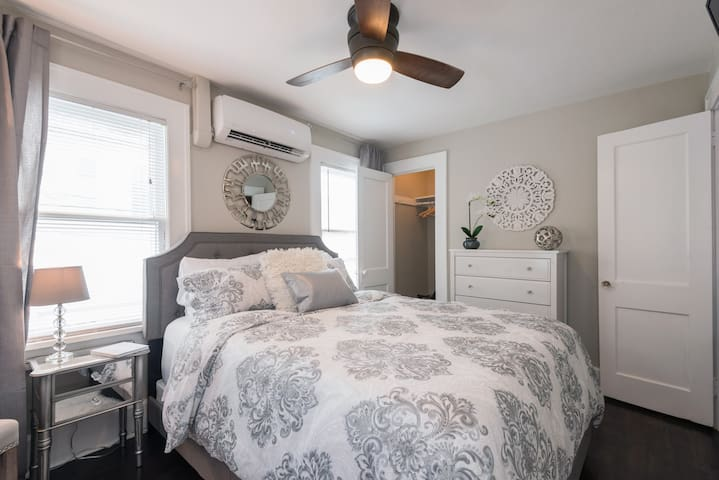 Bedroom with Queen size bed, walk-in closet and flat screen Roku TV with cable.