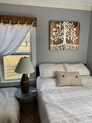 Bedroom 2 includes a full bed and a single bed, as well as furniture and art handcrafted for this space.