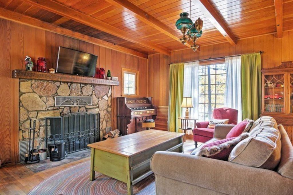Charming vintage style living room with hand built fireplace and antique 1890s foot pump piano.