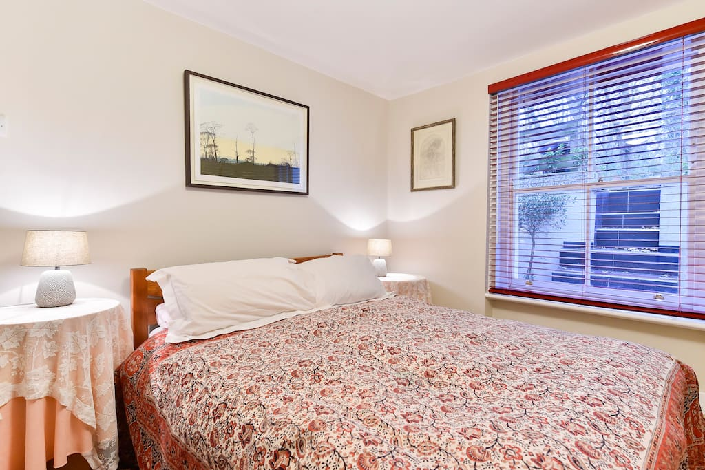 The bedroom contains a comfy king sized bed with bedside tables and lamps, a chair, plenty of storage and hanging space, and large window providing plenty of natural light.