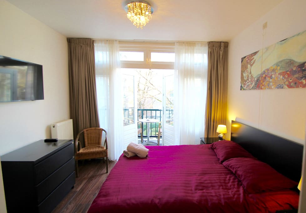 double bedroom with private balcony & flat screen smart TV