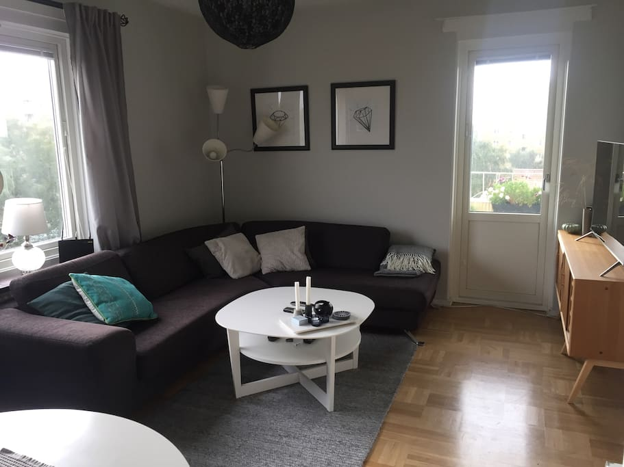 Livingroom with sofa, tv and door to the balcony