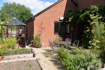 Rear courtyard style patio with eating area and herb garden. Great suntrap.