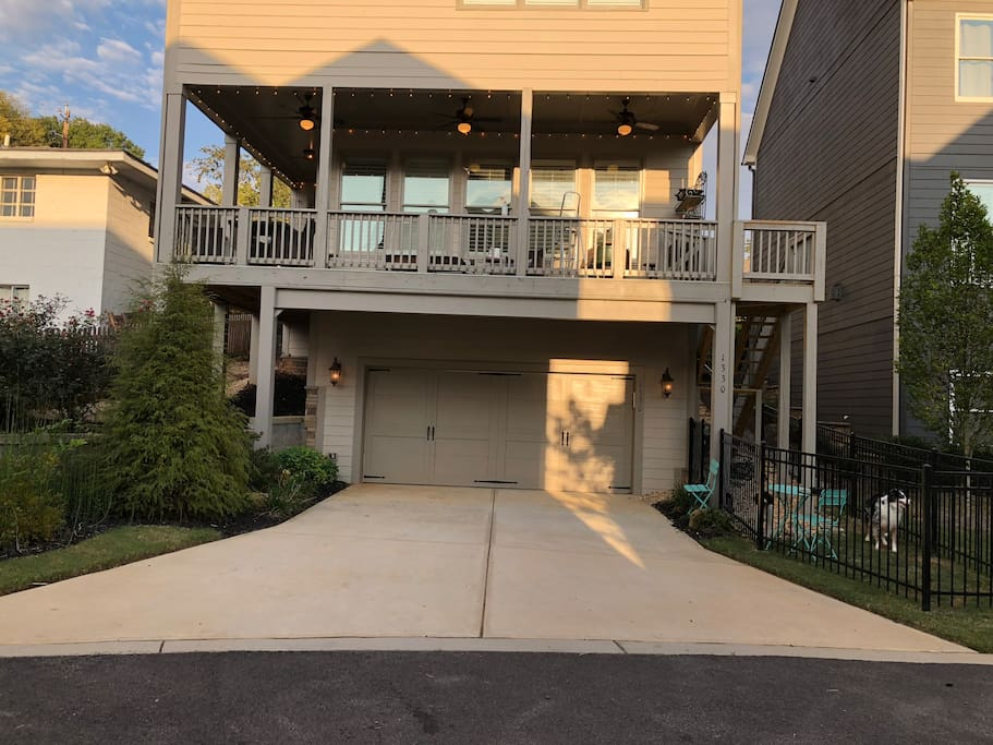 Rear property view where suite is accessed! Please be sure you are at the right location! Long drive, long covered porch wrapped  with Edison lights and stairs; ; garden area to the left; black fenced yard to right with bright blue table and chairs