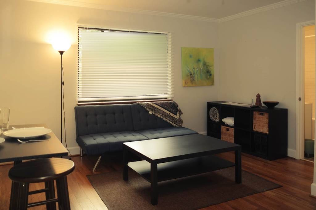 Living Room: You'll find a breakfast nook, the Futon couch/bed, ceiling fan, and flat-screen TV with a few local channels (off-photo, mounted on the wall). Extra blankets are stored in the shelving spaces along the back wall.