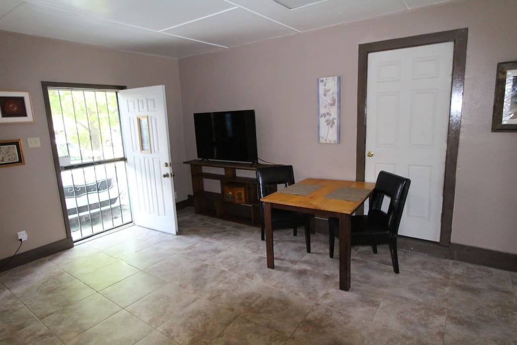 Apartment is furnished with dining table and television.