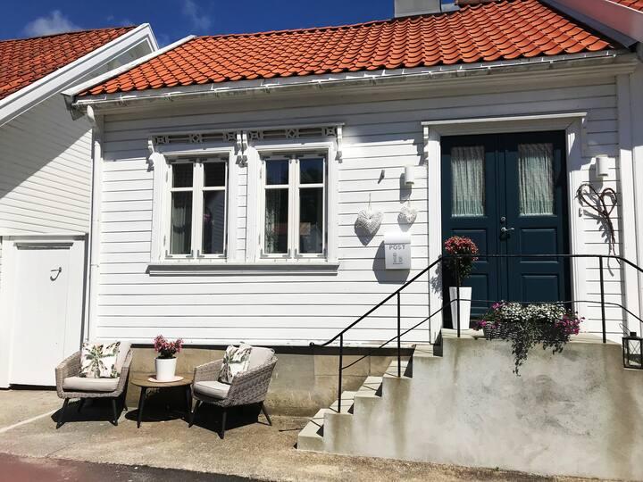 Koselig, lite sørlandshus med solrik bakgård