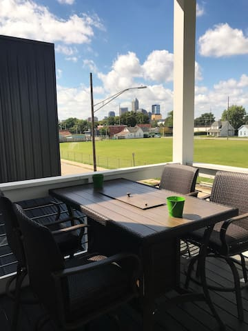 Upstairs balcony with bar top table and chairs overlooking the beautiful downtown city sky line.