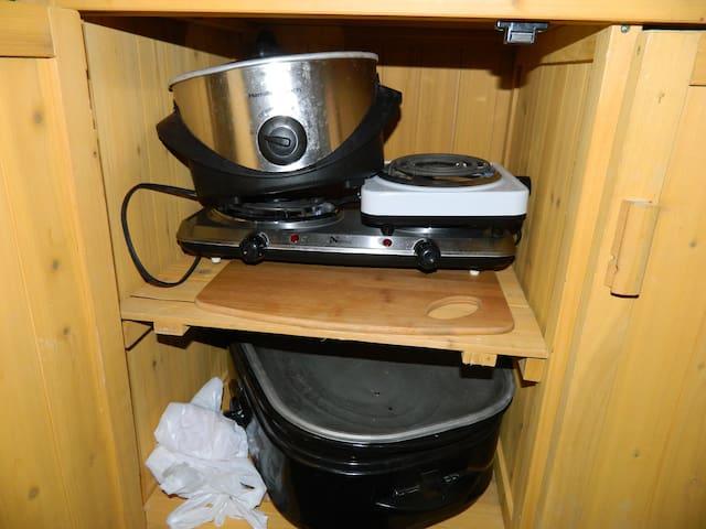 crock pot, hot plates, roaster oven stored underneath granite countertops