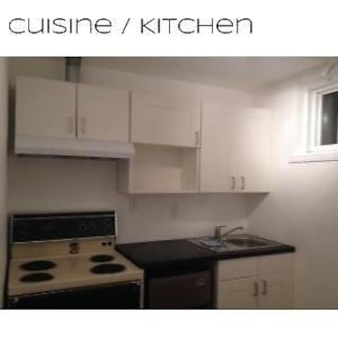Kitchen with fridge, stove, cabinets with dishes and pots to cool.