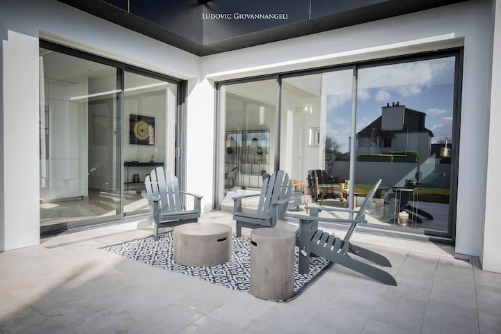 Une terrasse aménagée avec Fauteuils, Parasols, BBQ..