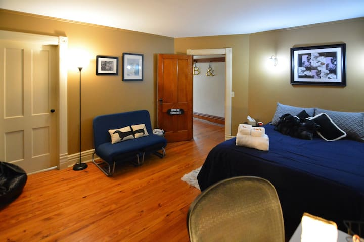 """Spacious """"Modern Traveler"""" bedroom equipped with comfortable desk for working or getting ready, as well as extra seating."""