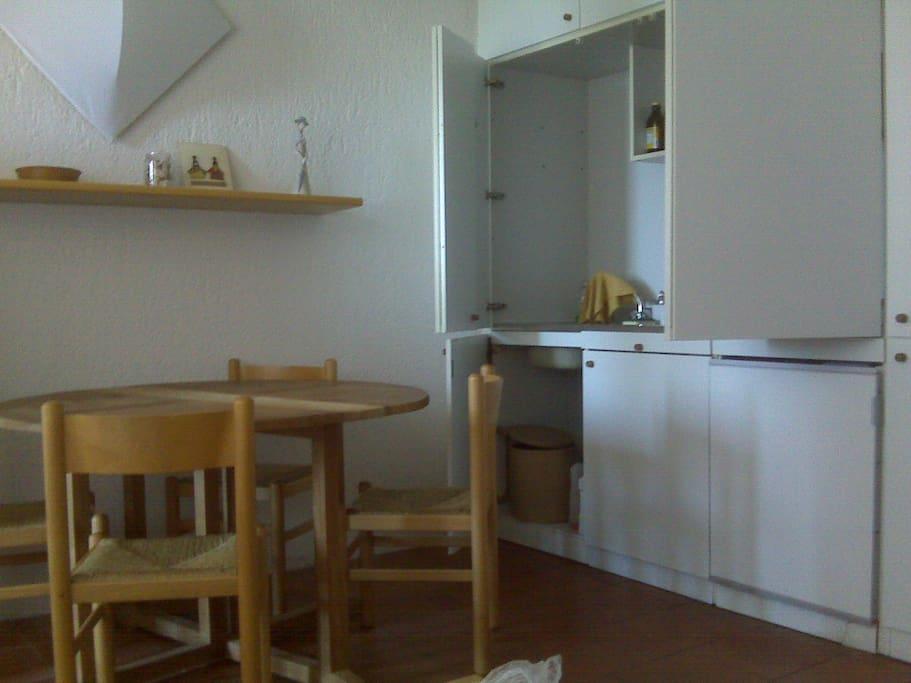 la cucina open space con tavolo con quattro sedie