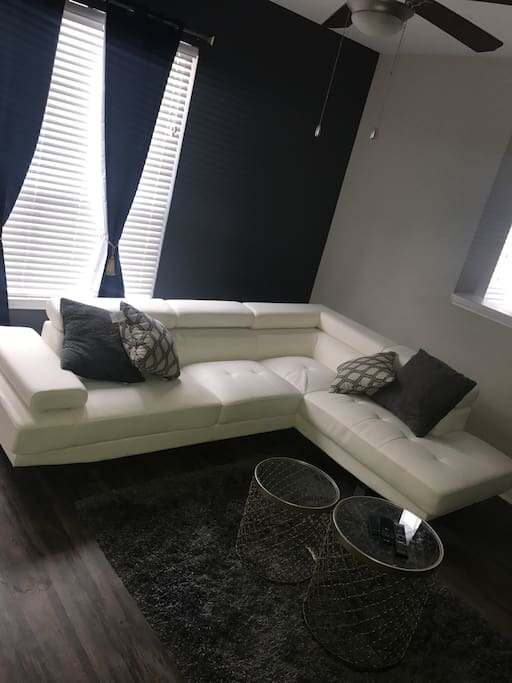 White leather sectional couch with adjustable headrest and armrest.