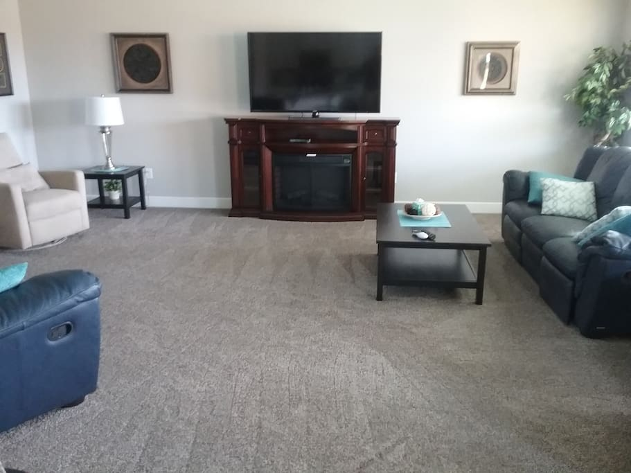 """Comfortable living room with 60"""" TV with DirectTV and fireplace."""