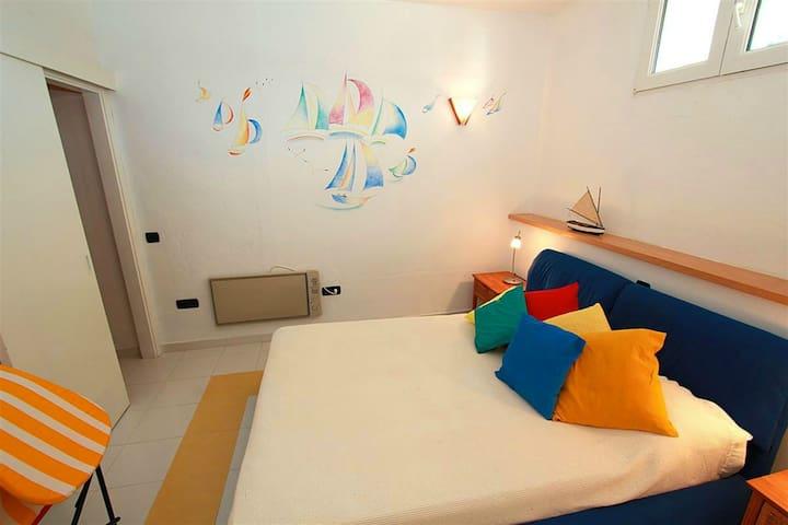 Camera da letto matrimoniale con cabina armadio en suite e un grande specchio.