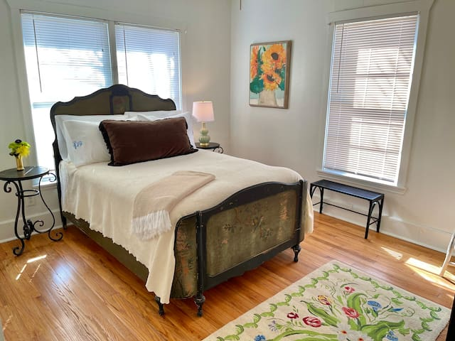 This front bedroom has an antique painted bed frame and double size mattress. The bed has high thread count sheets and Little Blue Bungalow monogrammed pillows. The throw laid across the bed is to add to your comfort throughout the home.