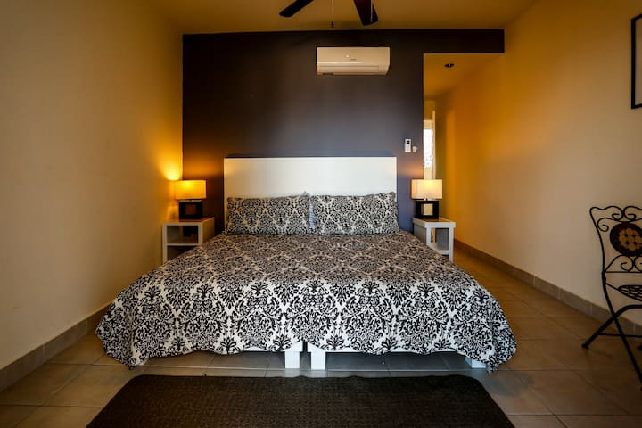Bedroom with king size bed, A/C and fan