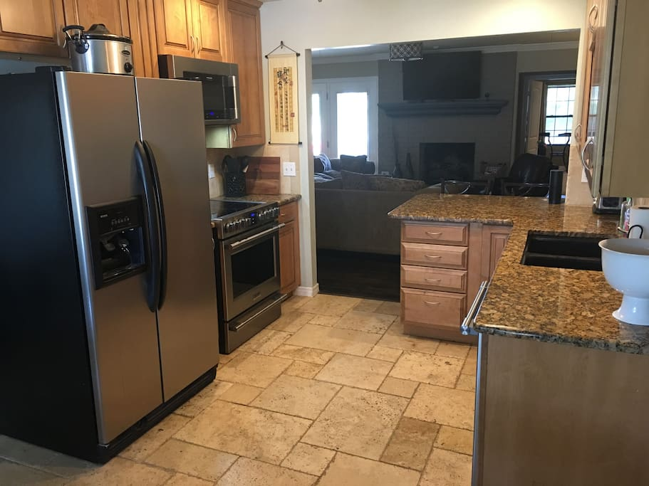 Open-concept kitchen with all new appliances and a granite countertops.