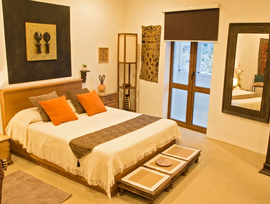 The large and spacious bedroom has a warm and comfortable feel to it.