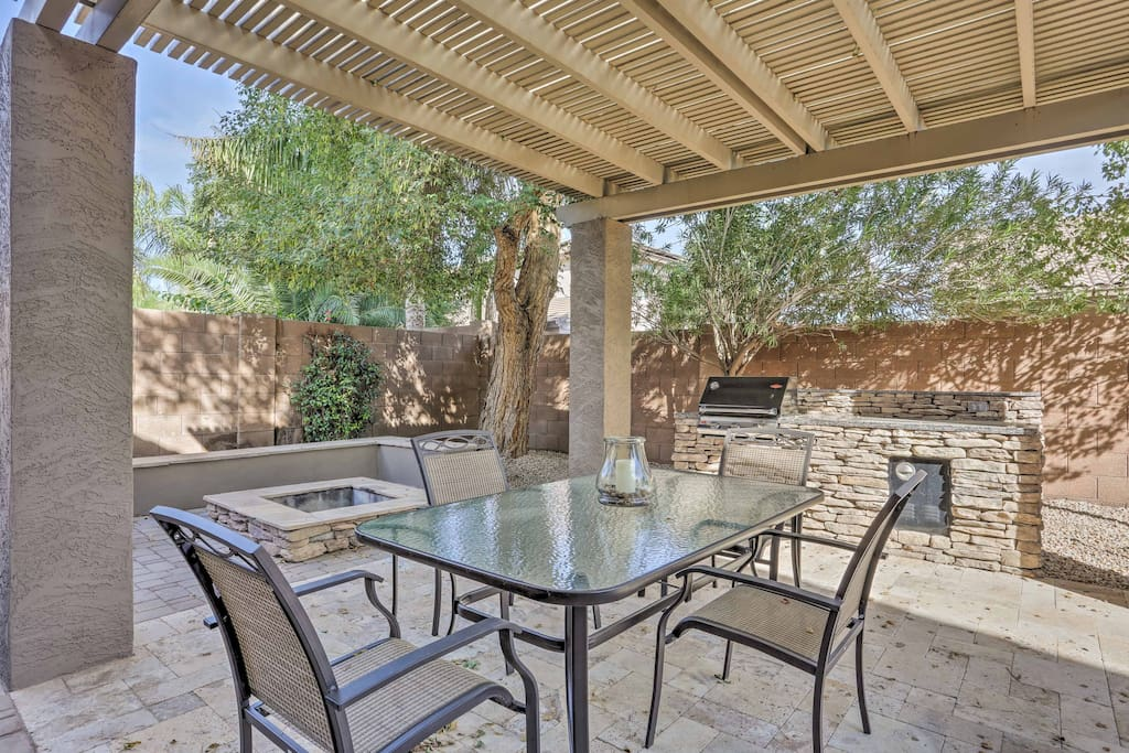 The home features wonderful interior and exterior living spaces to enjoy, including this pergola complete with a gas grill, fire pit and dining area!