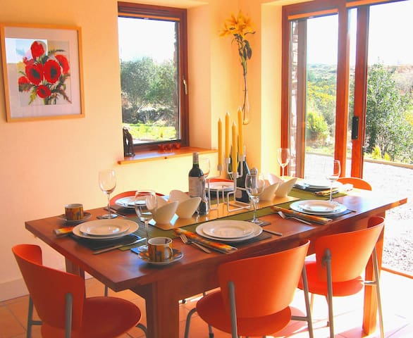 Sun streams into dining area with floor-to-ceiling windows & doors opening onto south-facing patio.