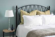 Comfortable queen-sized (extra length) bed with plush linen and blockout curtains.