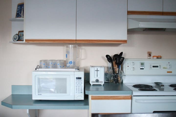 Microwave, toaster, stove and cooking utensils.