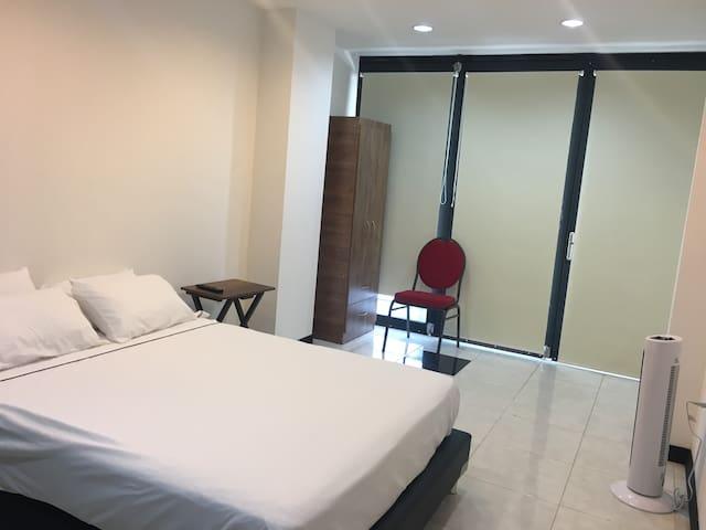 Comodo espacio con ventilador, mesa y silla auxiliar