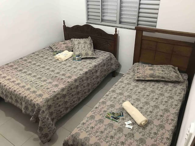 Quarto número 1: ventilador de teto, 1 cama de casal, 1 de solteiro. Com espaço sobrando.