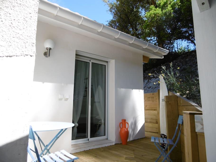 L'entrée de votre chambre et sa petite terrasse aménagée (table, chaises et chaises longues)