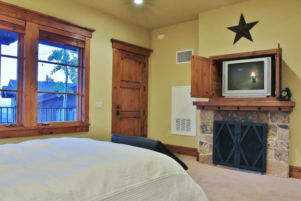 Living room/bedroom of lookout cabin with TV and fireplace