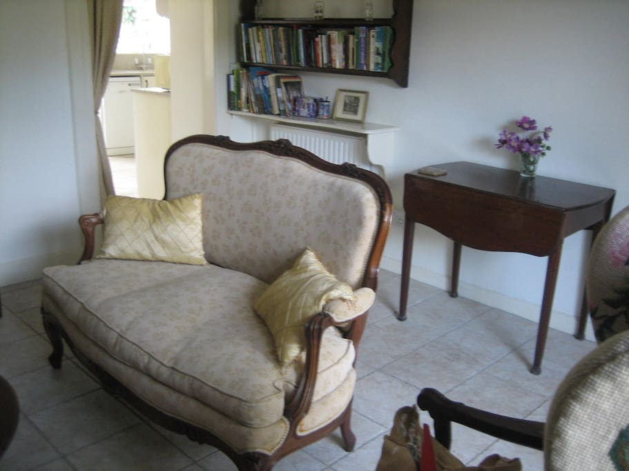 The front living room is bright and well-furnished. There is a large collection of books about Dorset
