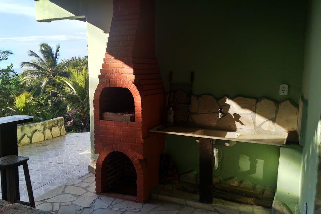 Área de lazer com churrasqueira, bancada com pia e lavabo