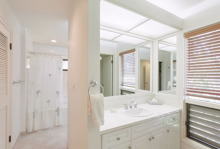 The master bathroom features two vanities with sinks, oversized soaking tub with shower, toilet, washer/dryer and closet