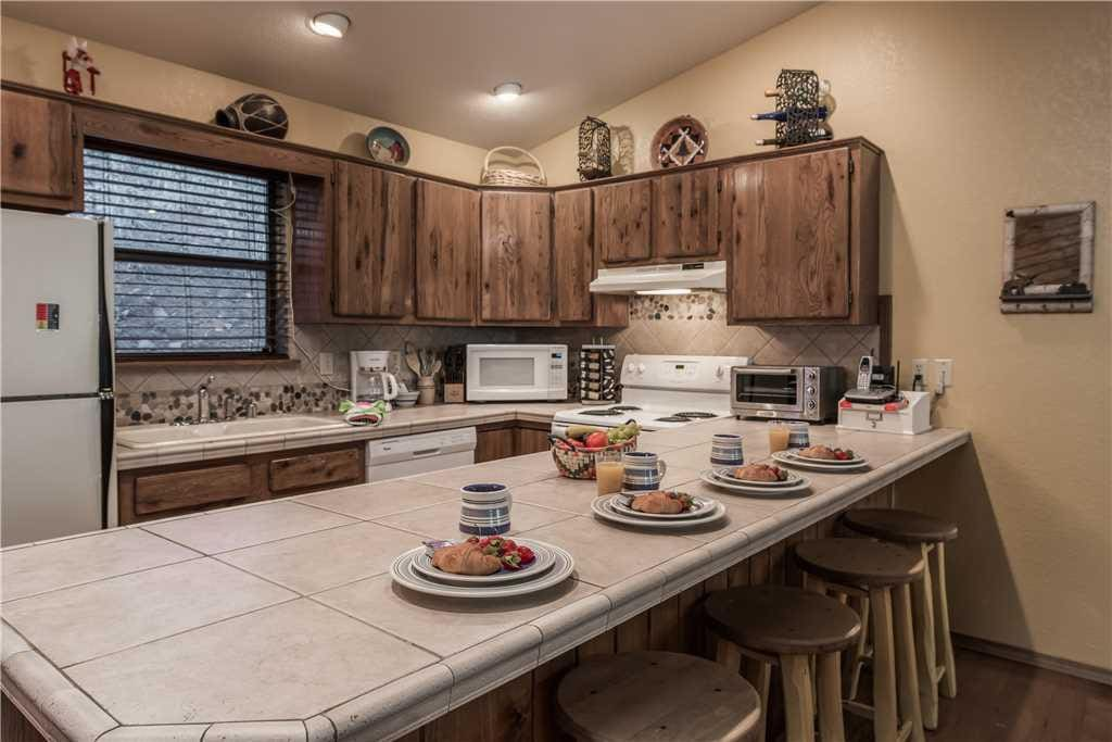 The open kitchen and breakfast bar are sure to be a hit with your guests.