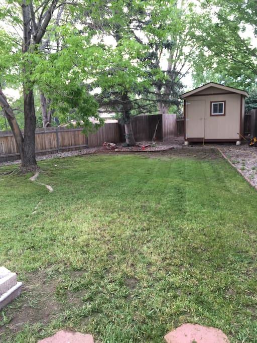 Private backyard with green grass and large shade tree. Have a BBQ on the concrete patio with grill, table and chairs