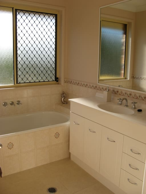 Bright, fully equipped private bathroom with bath and shower.  Separate toilet adjacent.